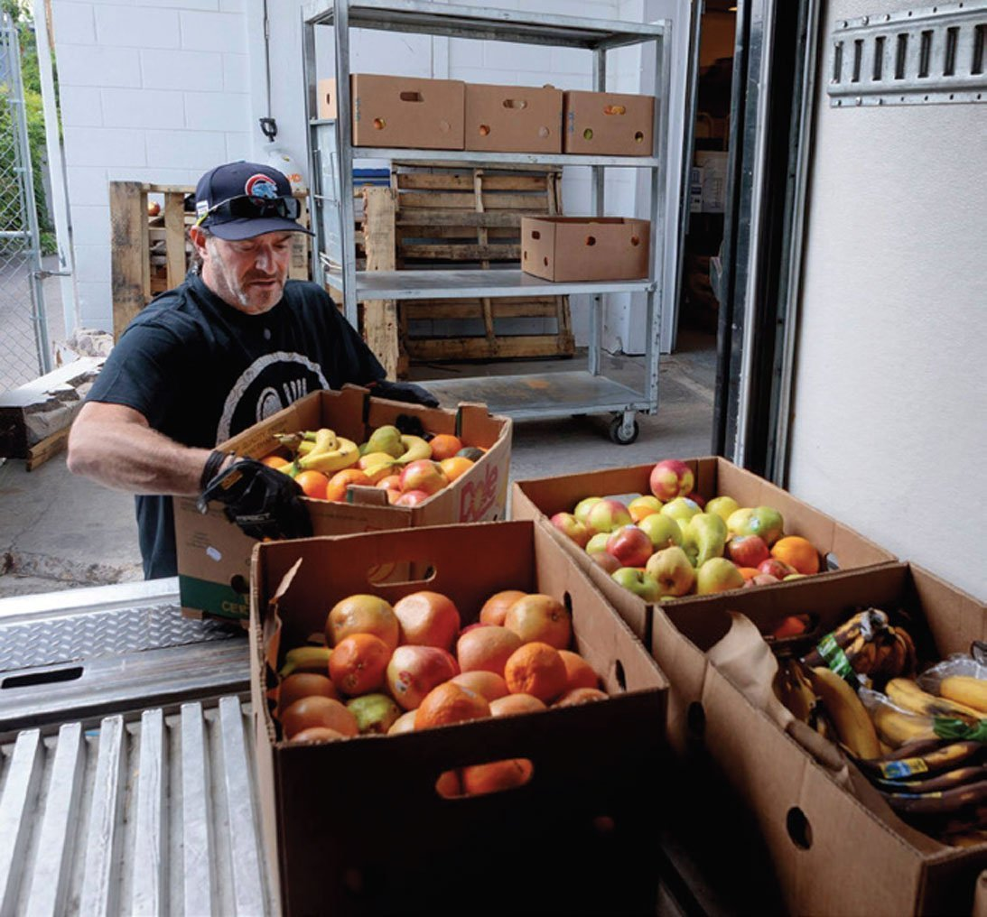 A man loading boxes of produce onto a truck.