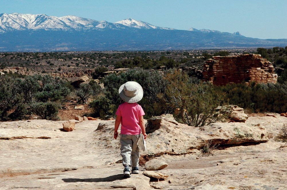 A child walking away from the camera, towards the mountains.