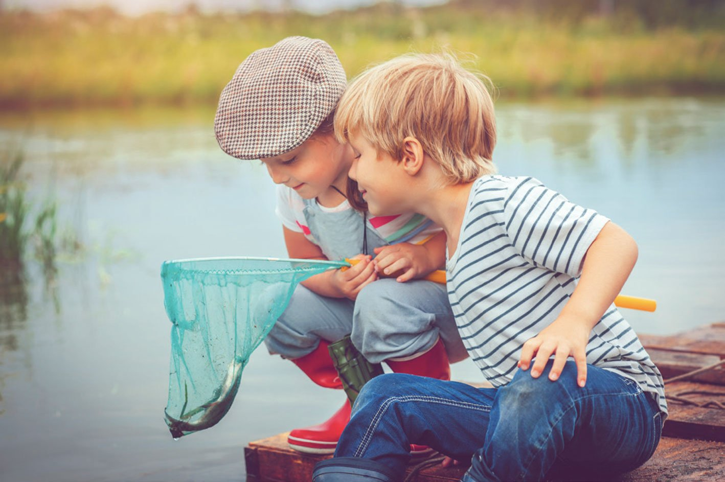 Two kids looking at a fish in a net.