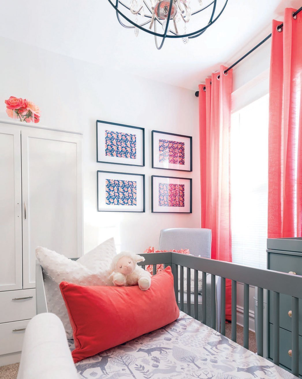 Stylish pink Nursery with a lamb stuffed animal in the crib.