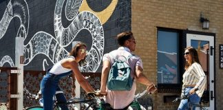 people-sitting-on-bikes-in-front-of-snake-mural